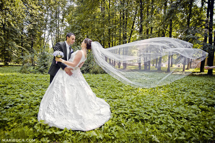 the groom to the bride looks like she flies a long white veil in the wind on a background of green grass and trees.