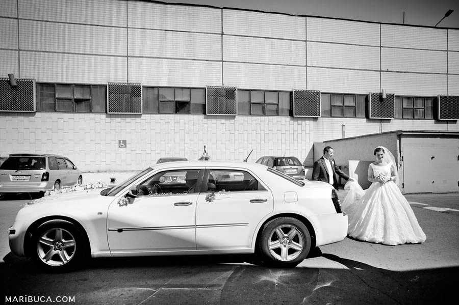 A black and white photograph of the bride and groom emerging from a white Bentley car against the backdrop of an industrial building.