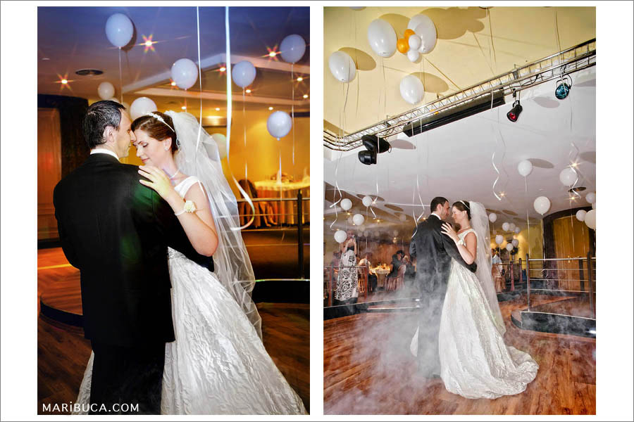 grooms the bride on the first dance in the hall on the background of white balls on the ceiling