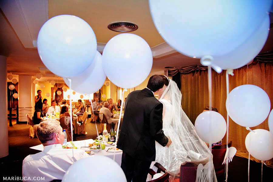the bride and groom are kissing in the restaurant on the background of white balls in the hanging air and guests in the background.