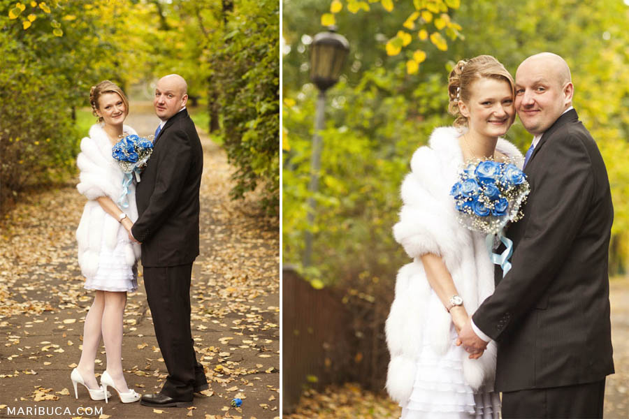 the groom in a black suit, the bride in a white short dress, a fur cape and a light blue bouquet walk in the park