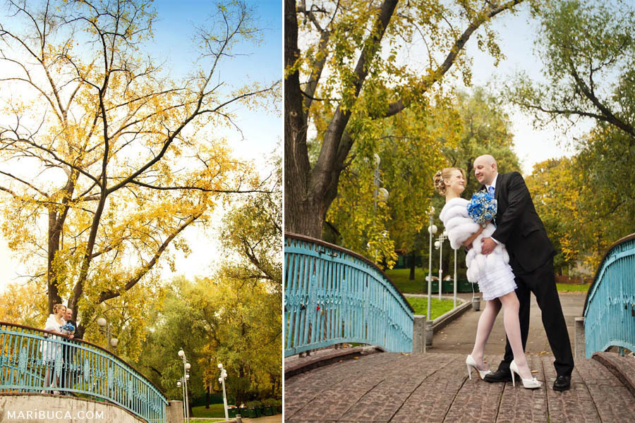 the bride and groom are standing on the bridge brown with turquoise accents on the background of yellow-green foliage