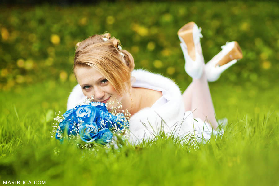 bride in white dress, white shoes and with a blue wedding bouquet lies on the green grass on the background of yellow flowers
