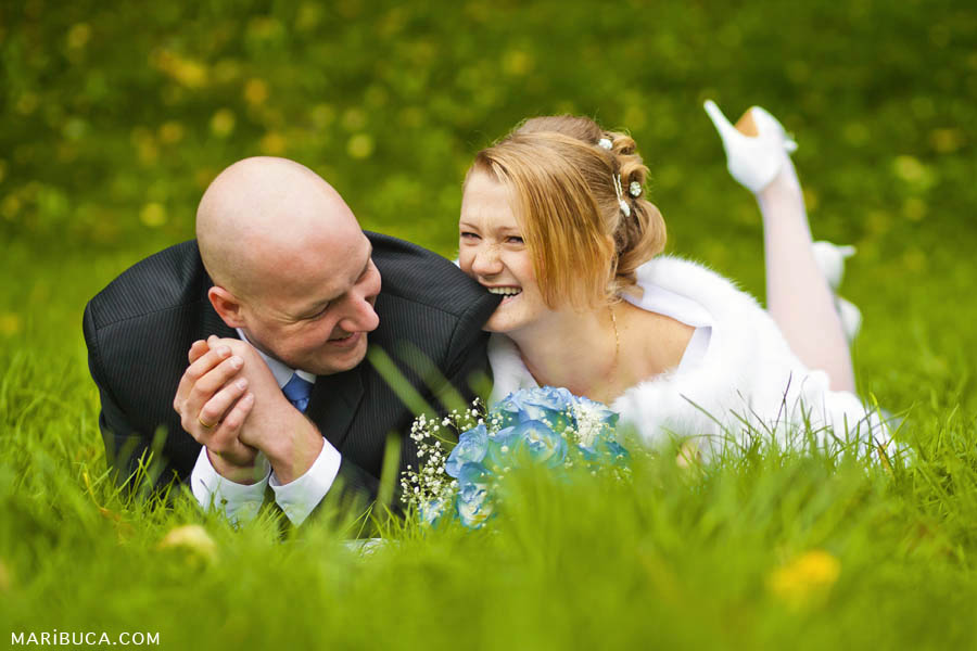 The bride bites the groom's black jacket and they both laughs lying on the green grass surrounded by yellow flowers.