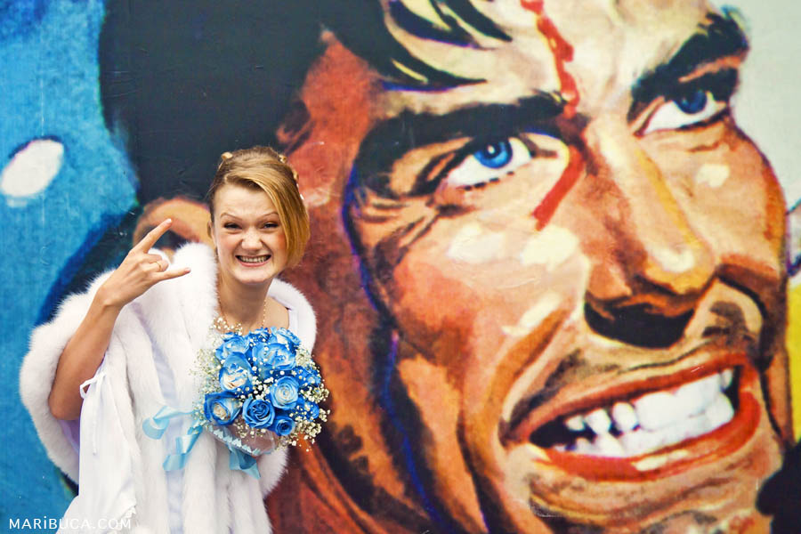 The bride shows a gangster style on the background of an art street picture with a man's face.