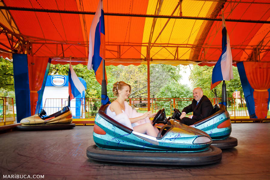 the bride and groom take a ride in the amusement park