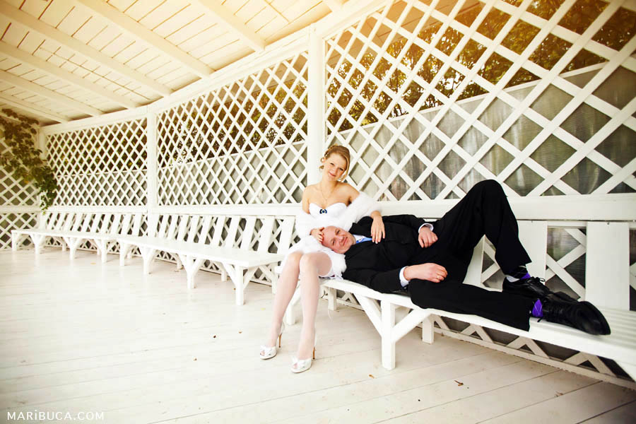 Bride and groom sitting lying on white bench in a white large gazebo