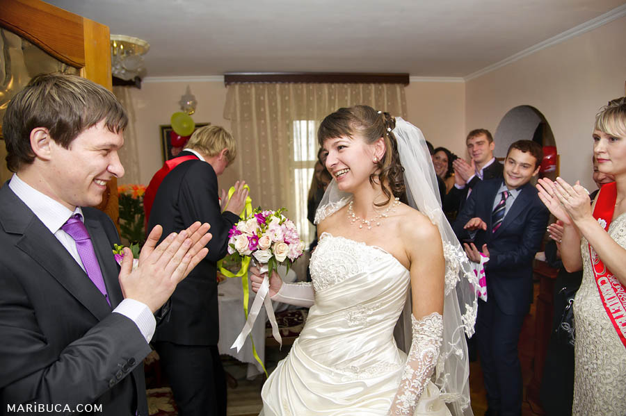 The bride and groom dance at home in her apartment and guests clap hands.