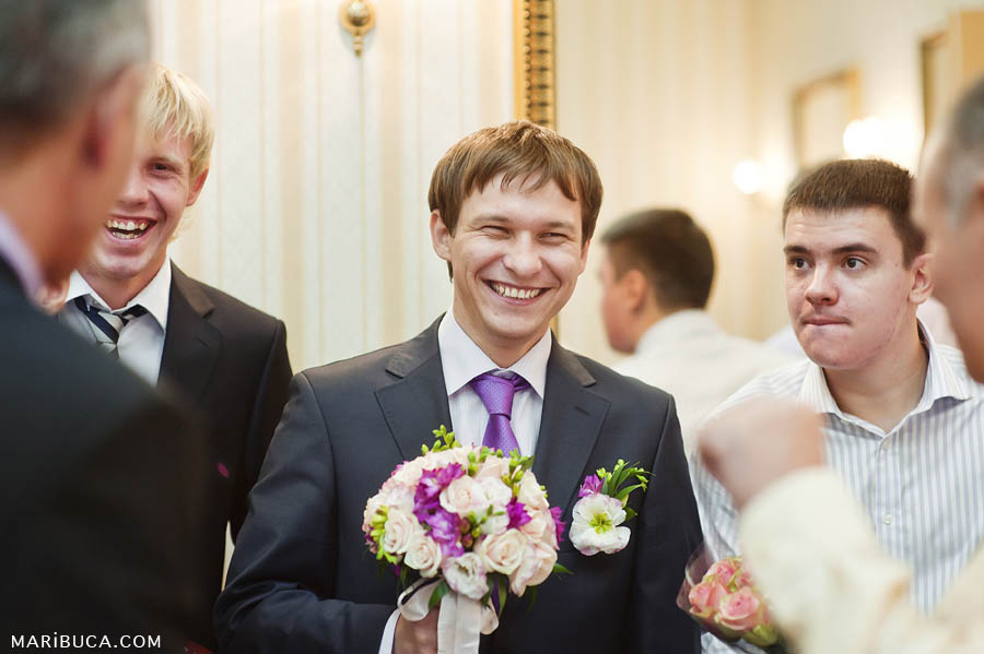 The groom laughs with friends in the registry office