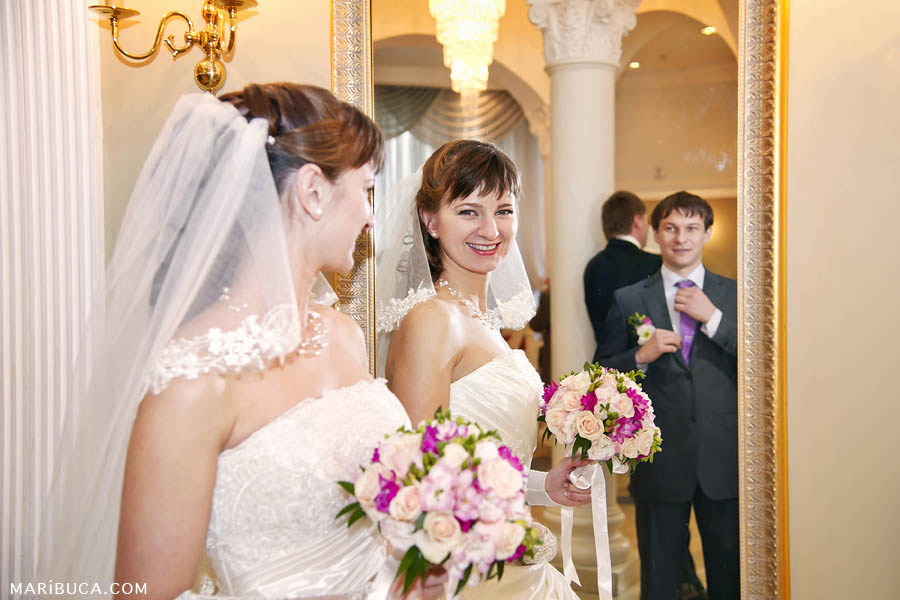 The bride looks at herself in the mirror and sees the groom in a reflection in the registry office