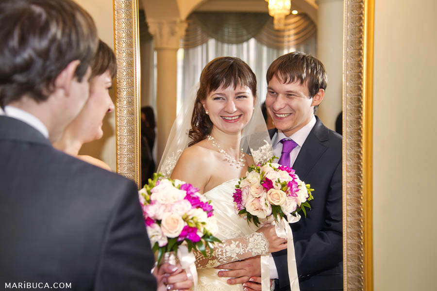 The bride and groom together look at themselves in the mirror in the registry office.