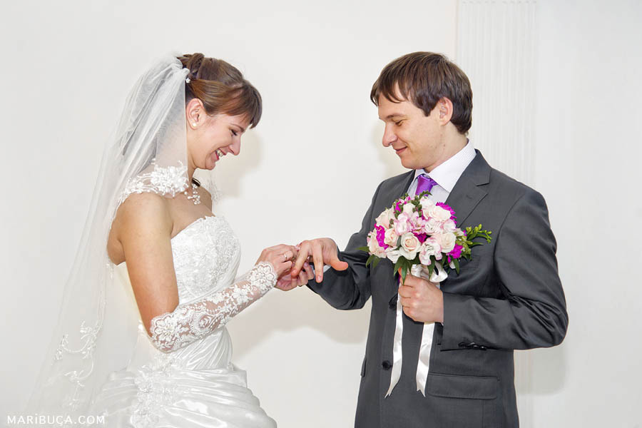 The groom puts the ring on the bride's finger in the wedding ceremony on the background of a white wall