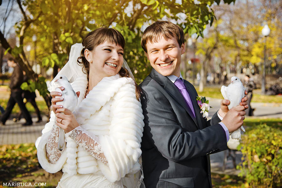 Bride and groom are standing back to each other holding white pigeons