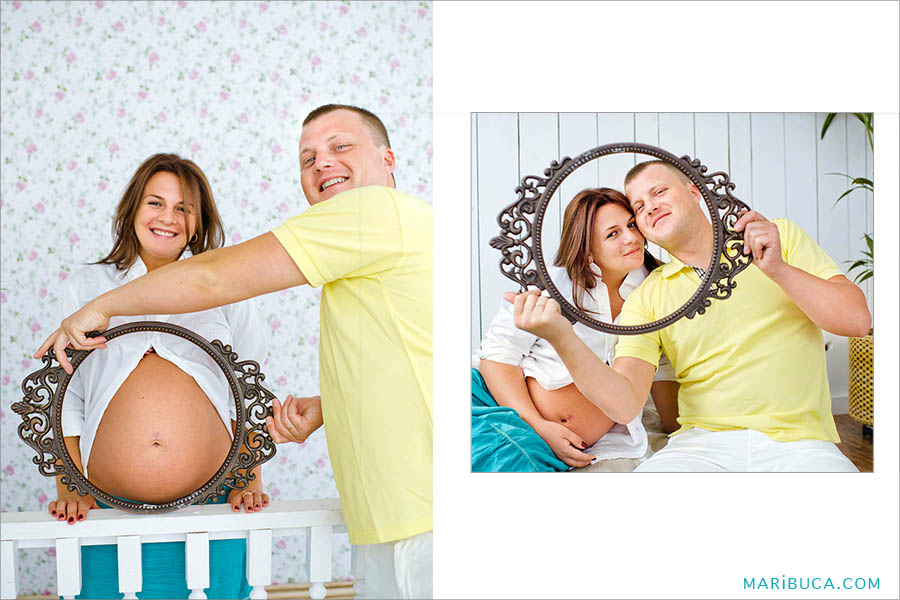 The guy holds a round frame in front of his wife's belly and they are expecting a baby!