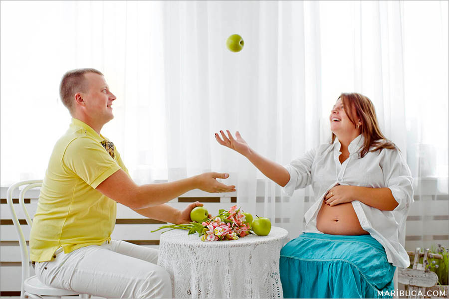 Maternity photographing a girl throws up green apples and a young man catches them