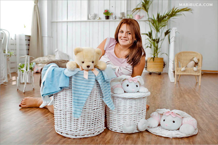 The pregnant girl surrounded white baskets, light blue clothes for future baby and soft white and beige toys.