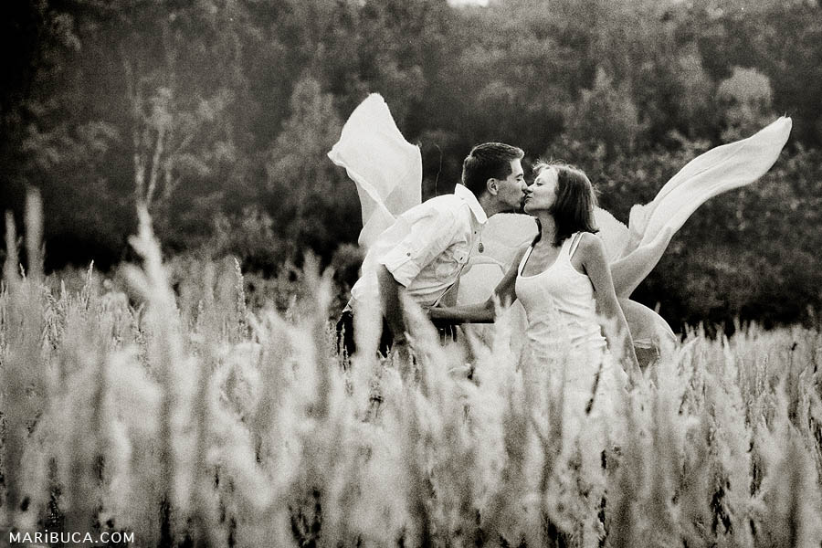 black and white photos of a girl with a guy standing above tall grass - kissing and behind them the fabric flies in the cloth of wings.
