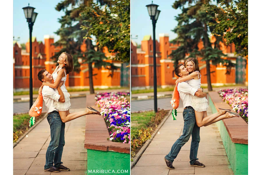 young husband lifted his young wife in his arms. The couple laughs and celebrate their anniversary in the first rays of the sunrise in the park.
