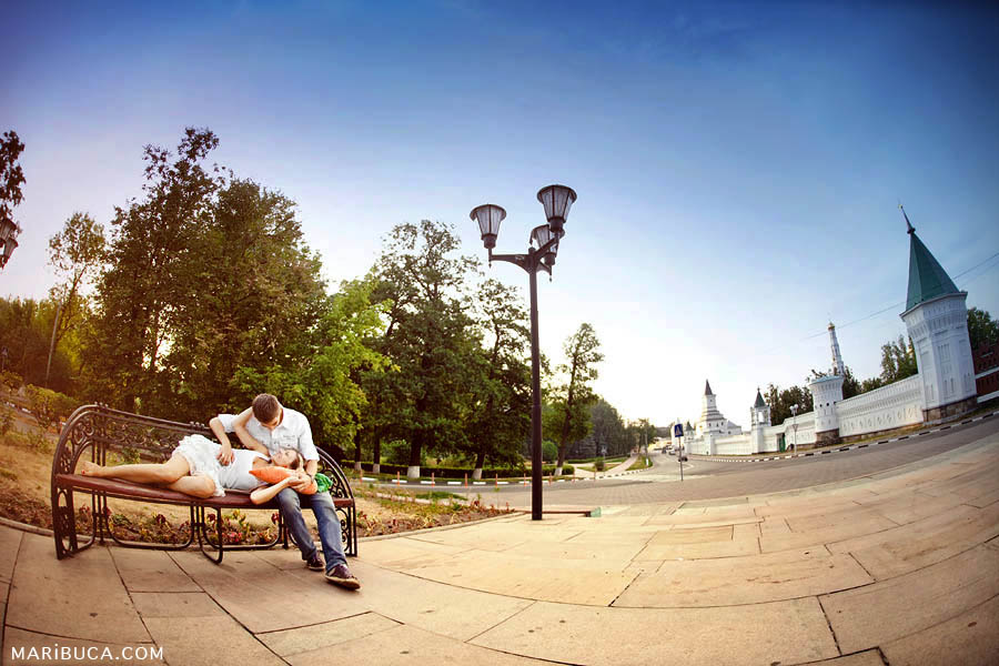 A couple enjoy a company of each other and they lay down in the bench against the background of the white church and the blue sky.