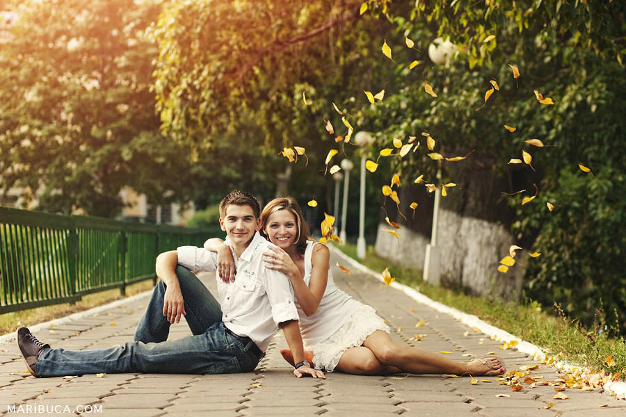the girl and the guy are sitting on the asphalt against the background of falling yellow leaves in the park in summer weather.