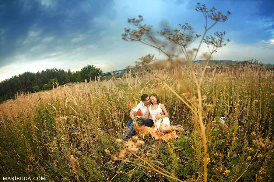 Couple's wedding anniversary at dawn on the lawn with high yellow grass and blue sky at a photoshoot in Livermore