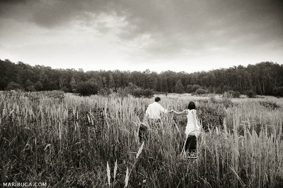 Photo retro of couple are dragging chairs on the meadow with tall grass and the forest background