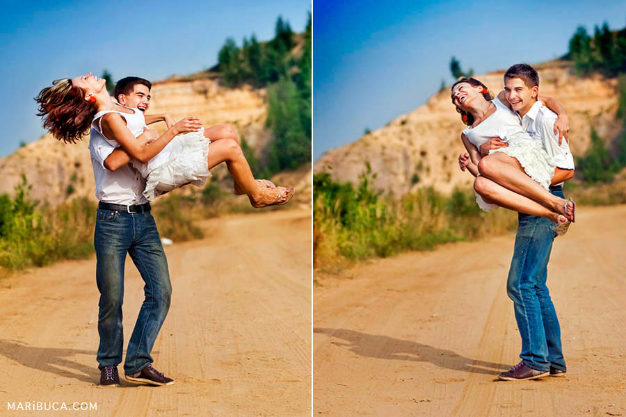 wedding anniversary in livermore. The guy lifted her into his arms and turns her against a background of beige-yellow mountains and yellow sand in sunny weather.