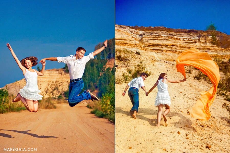 A married couple is jumping against the background of the yellow mountain, sand and blue sky. The boys climb on the hill waving his long orange cloth in Bay Aria.