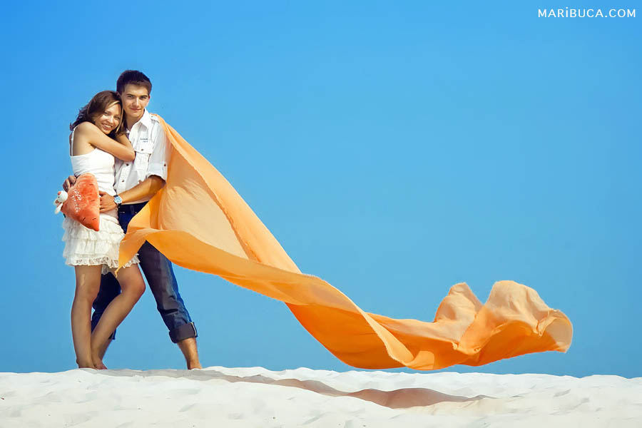 The white theme of the anniversary wedding couple with developing orange long clothes as contrast blue sky and white sands.