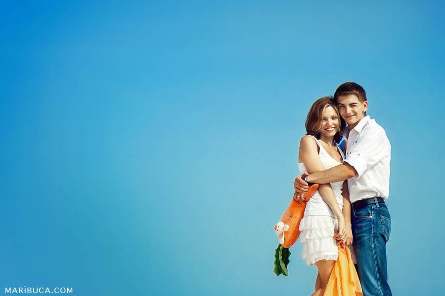 Portrait anniversary wedding couple hug and happy against the fabulous blue sky.