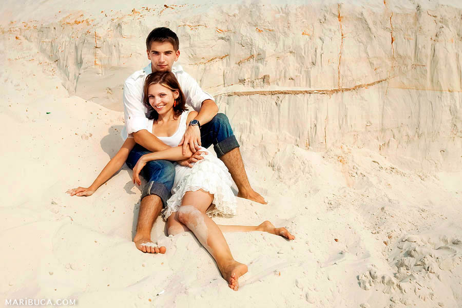 Perfect day and the wonderful married couple is hugging each other against the background of almost white sand.
