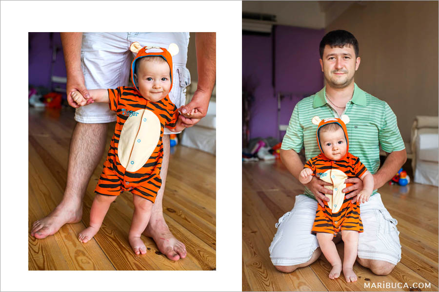 dad with 8 month old son who stands before him on a beige background.