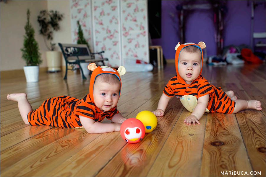 eight month old twin boys dressed in orange tigers are lying on a beige floor and playing red and yellow ball.