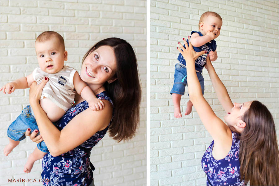mother holds and throws baby sons twins up against the white brick wall.