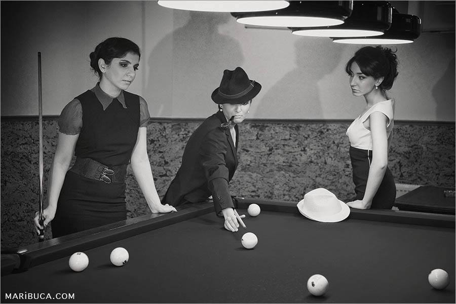 black white photo of three girls are playing billiards. One of the three girls in a black hat and a man's jacket with a pipe in her mouth hits a billiard ball.