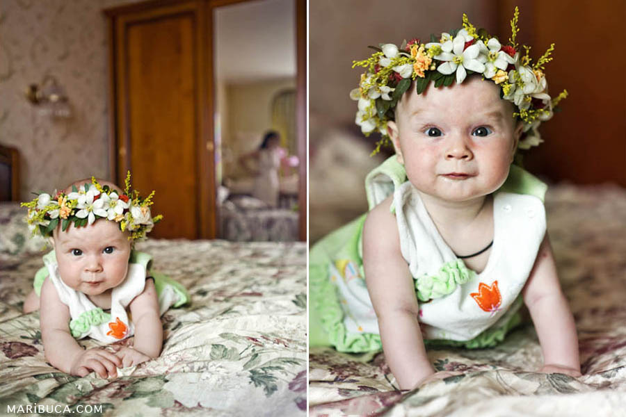 A cute little five-month-old girl with a wreath of natural flowers on her head is lying on the bed and smiling slightly.