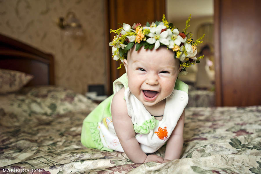 five-month girl standing on her arms with a wreath on her head and laughing at home