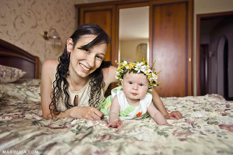 portrait of mother and her sweet five-month daughter with a wreath on his head against the background of the home.