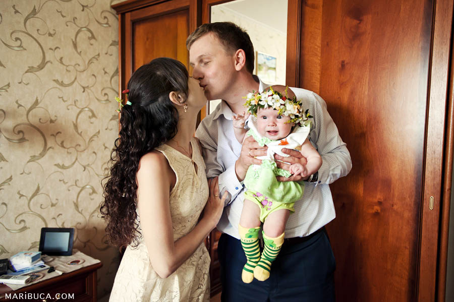 mom and dad kiss each other, dad's holds five-month daughter in the home environment