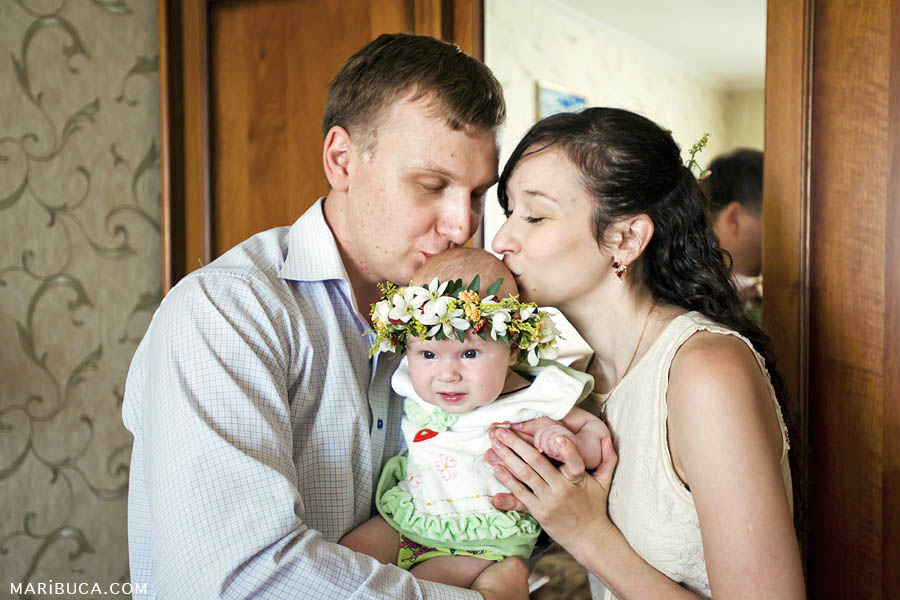 parents kiss the baby daughter in the top of the head, the daughter has a wreath with fresh flowers on her head.