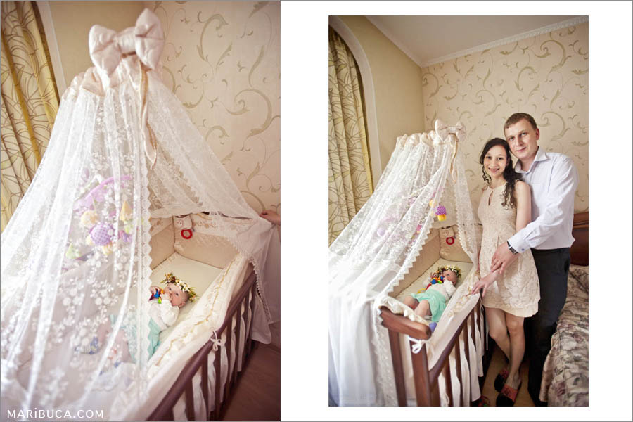 parents stand next to the bed of a five-month-old daughter who lies in a beautiful bed with a white curtain.