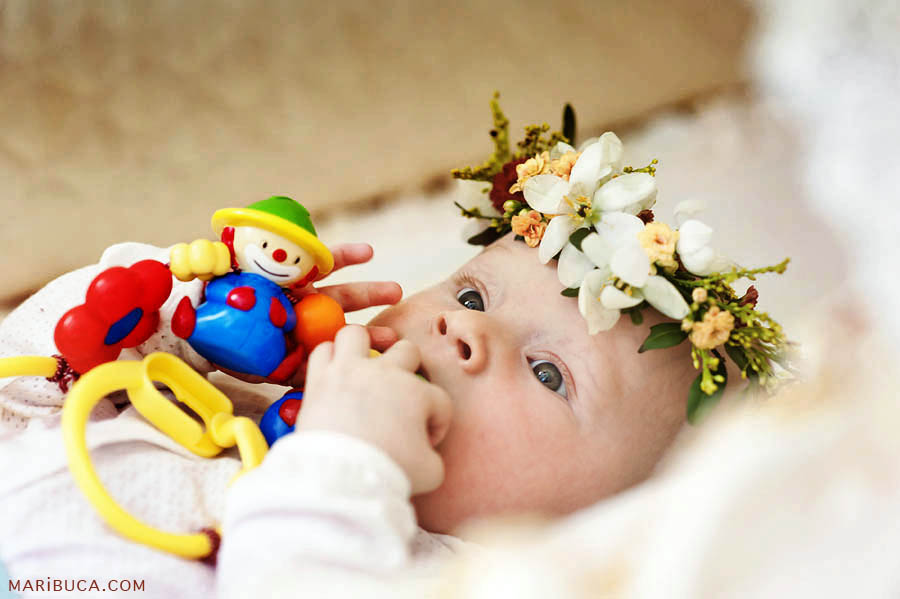 Ther five-month-old daughter who wears a wreath with fresh flowers and hold the bright toy.