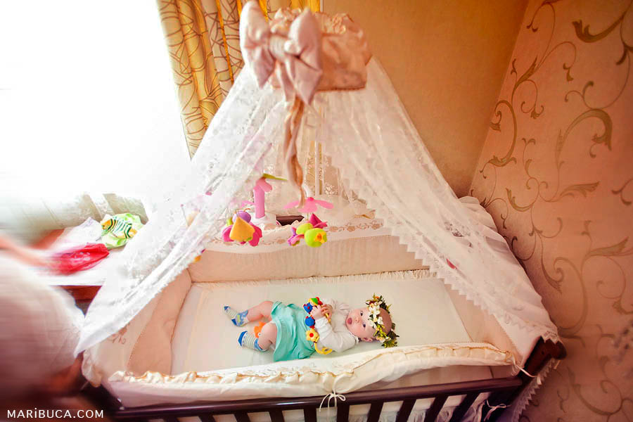 five month old baby girl is lying in a crib in the form of a tent