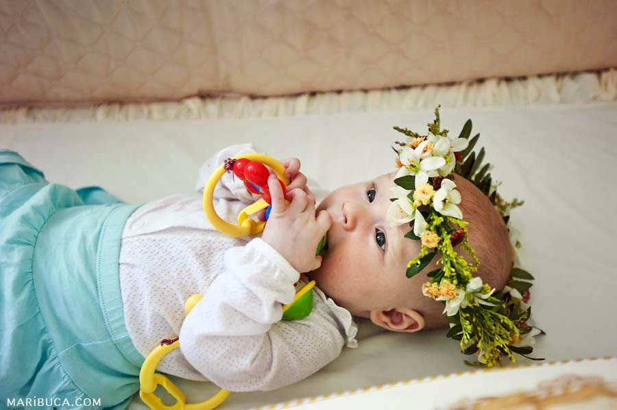 little girl is lying on her back in a white jacket and turquoise skirt on a white background and chews bright rattle in the crib