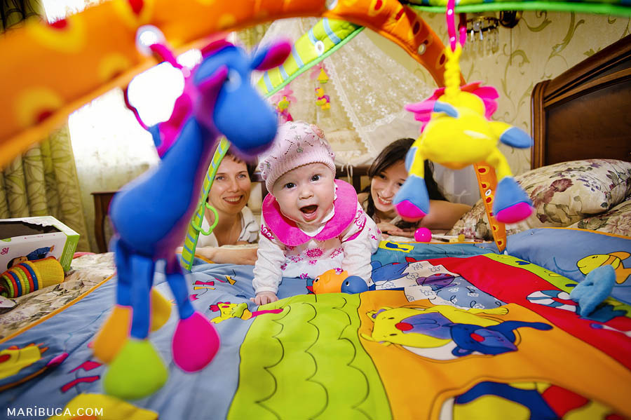 mother and aunt look at baby girl who is excited in the environment of bright and color game mat with toys.