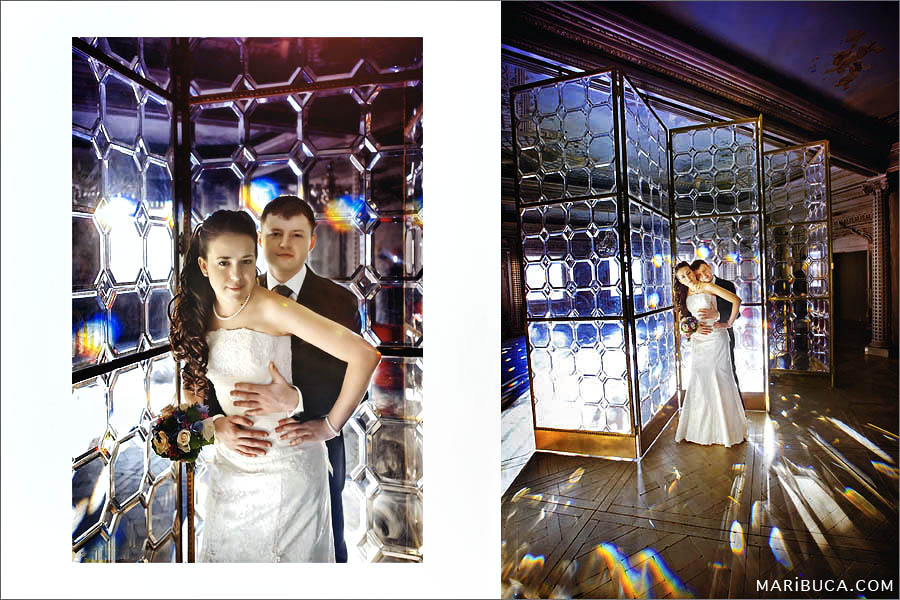 The bride and groom are standing in front of a large glass screen with rays and reflection of light.