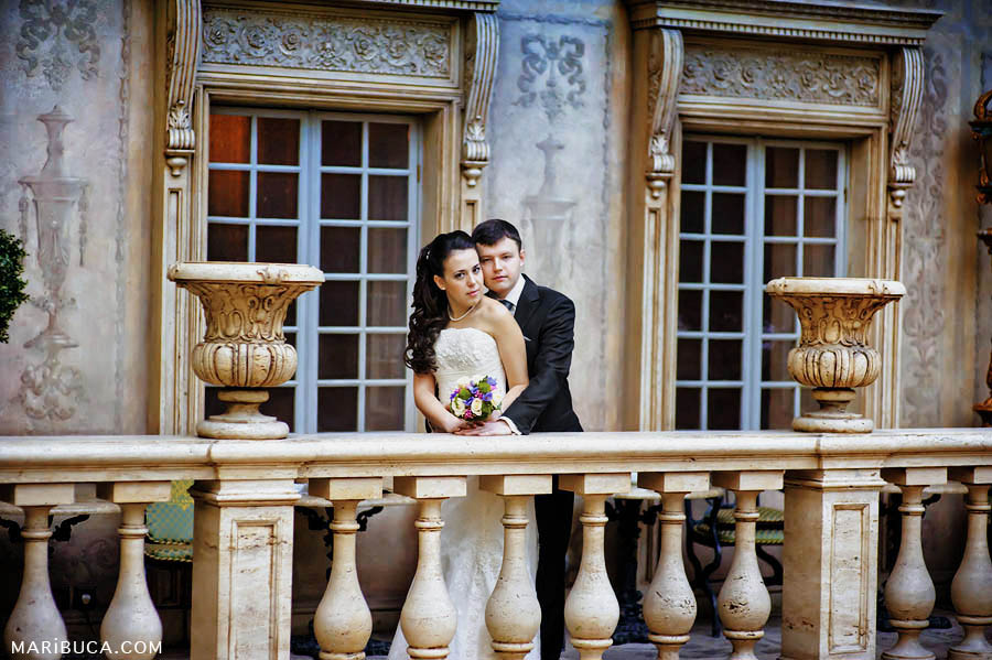 the groom embraced his wife against the background of textured railings and stone vases as if they were in a museum.