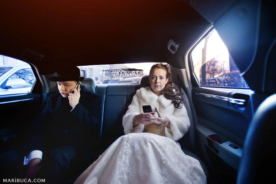 newlyweds-sit-limo  portrait of the bride and groom in the car. The bridegroom in a black hat and coat talks on the phone, the bride has serious look..