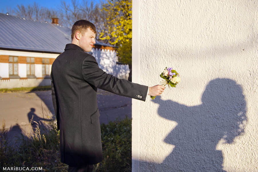 The groom passes the bouquet to the bride, the bride picks up the bouquet as a reflection from the sun on the wall.