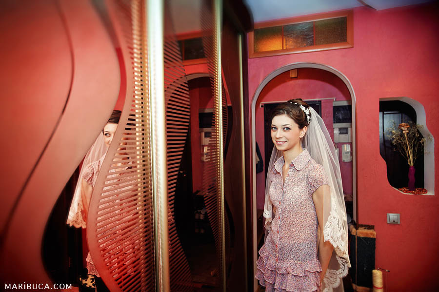 The bride looks herself in the mirror in the red walls background